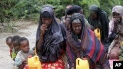 Kinamama na watoto wa Kisomali wakisubiri misaada katika kambi moja ya waliokosa chakula nje kidogo ya Mogadishu, Somalia