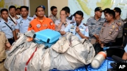 Commander of Indonesian Air Force 1st Operational Command Rear Marshall Dwi Putranto, center, shows the airplane parts and a suitcase found floating on the water near the site where AirAsia Flight 8501 disappeared, during a press conference at Pangkalan Bun, Central Borneo, Indonesia, Tues., Dec. 30, 2014. (AP Photo/Dewi Nurcahyani)