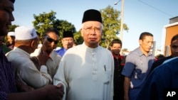 FILE - Malaysian Prime Minister Najib Razak arrives for a Ramadan breakfast at a mosque in Semenyih outside Kuala Lumpur, Malaysia. Malaysia's anti-corruption agency has questioned Najib over deposits of nearly $700 million funds made to his personal bank account.