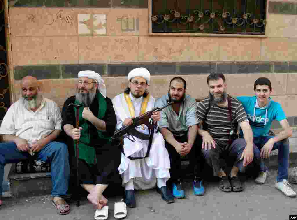 Sheikh Abu Rateb (2nd-R), the head of the Right Brigade, poses with other protesters during a demonstration against the Syrian regime after the Eid al-Fitr prayer in Homs, August 8, 2013.