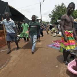 Ethnic Gueres carry a dead relative inside a temporary refugee camp set up at a Catholic church in Duekoue, Ivory Coast, May 2011.