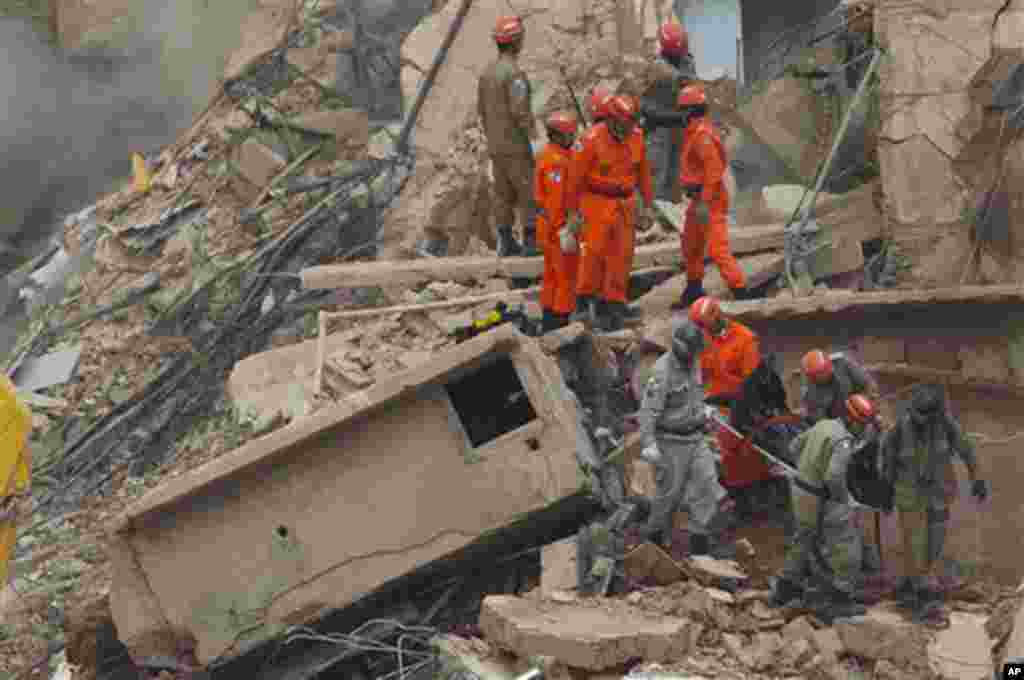 Rescue workers carry the body of a victim the day after a building collapsed in Rio de Janeiro, Brazil. January 26, 2012. (AP)