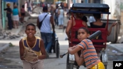 FILE -Youths play baseball in the streets of Old Havana, Cuba, June 11, 2013.