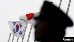 一名日本警察站在東京一家飄揚著日韓國旗、正在舉行日韓關係正常化50週年慶祝儀式的酒店前執勤。 (2015年6月22日)
