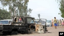 People drive past a burnt-out truck in Maputo, Mozambique, 04 Sep 2010