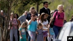 Mourners arrive at the Floresville Event Center to attend a funeral for members of the Holcombe family who were killed in the Sutherland Springs Baptist Church shooting, Nov. 15, 2017, in Floresville, Texas.