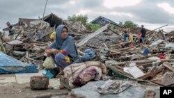 Una mujer sobreviviente del tsunami sentada sobre los escombros mientras intenta rescatar artículos del sitio donde estuvo su casa en Sumur, Indonesia, el 24 de diciembre de 2018.