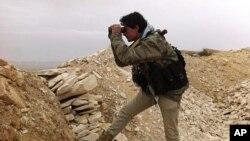 Một chiến binh quân nổi dậy quan sát tình hình chiến sự tại một tiền tuyến của thị trấn Yabroud, ngày 13 tháng 3, 2014.