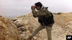 In this photo, which has been authenticated based on its contents and other AP reporting, a Syrian rebel looks through his binocular at one of the frontline of Yabroud town, the last rebel stronghold in Syria's mountainous Qalamoun region, Mar. 13, 2014. (Photo taken and provided by Local Comity of Yabroud Town)