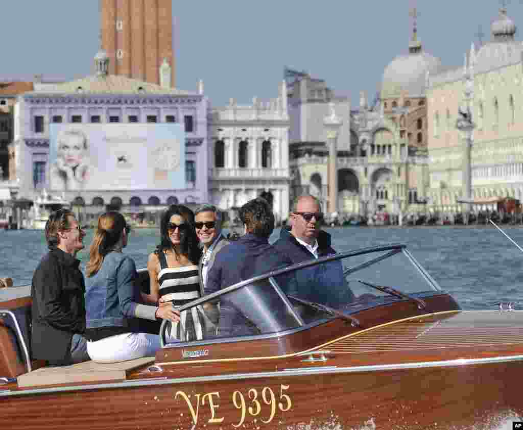 George Clooney, third right, his fiancee Amal Alamuddin, Cindy Crawford and her husband, Rande Gerber, boat past St. Mark's Square as they arrive in Venice, Italy. Clooney and Alamuddin are expected to get married this weekend in Venice, one of the world's most romantic settings.