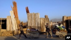 Afghan men pull their carts pass roadside timber stalls in Kabul, Afghanistan, Tuesday, June 21, 2011. (AP Photo/Gemunu Amarasinghe)