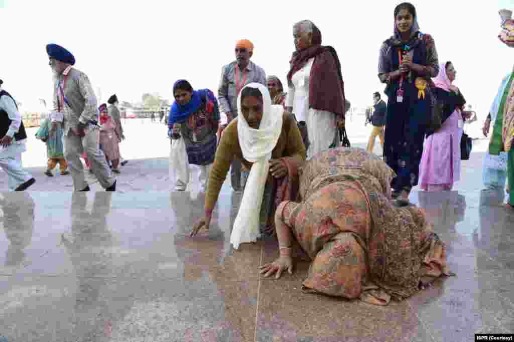 بھارت سے بذریعہ 'کرتار پور راہداری' پاکستان پہنچنے والے سکھ یاتری بابا گرو نانک کے مزار پر سجدہ ریز ہو رہے ہیں۔