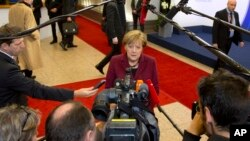 FILE - German Chancellor Angela Merkel speaks with reporters as she arrives for an EU-Turkey summit at the EU Council building in Brussels, Nov. 29, 2015.