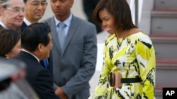 U.S. first lady Michelle Obama, right, is greeted by an unidentified Japanese official upon her arrival at Haneda International Airport in Tokyo Wednesday, March 18, 2015. (AP Photo/Shizuo Kambayashi)