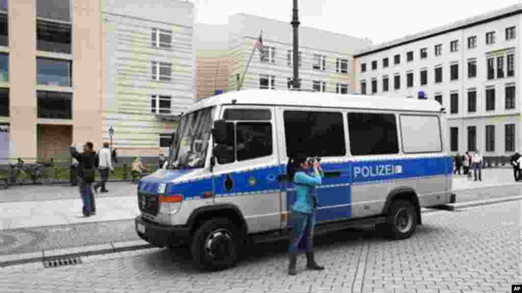 Tourists take pictures near a German police car guarding in front of the United States embassy in Berlin.