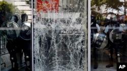 Полицейские блокируют разбитую демонстрантами стеклянную дверь. Гонконг, 1 июля 2019 г.