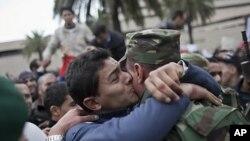20일 튀니스에 있는 집권여당 입헌민주연합(RCD) 사무실 앞에서 시위가 벌어진 가운데 한 시위자가 군인과 포옹하고있다.