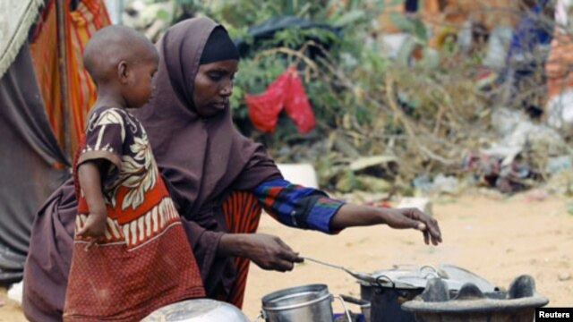 A Somali woman cooks food for her children in a camp set up for internally displaced people in Dinsoor, January 5, 2012.
