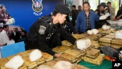 FILE - Thai policemen arrange packages of confiscated methamphetamine on a table before a press conference in Bangkok, Thailand, Feb. 15, 2013.