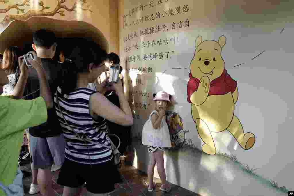 2018年8月8日,在上海的一幅描绘小熊维尼的壁画前面,一名儿童摆姿势拍照。改编自迪士尼经典动画《小熊维尼》的真人版电影《挚友维尼》在中国没拿到放映许可,从而被拒于全球第二大电影市场之外。