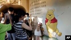 Một em nhỏ chụp hình với bức bích họa chú gấu Winnie the Pooh ở Thượng Hải, Trung Quốc, ngày 8 tháng 8, 2018.