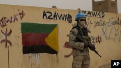 FILE -A U.N. peacekeeper stands guard at the entrance to a polling station in Kidal, Mali. A peacekeeper allegedly shot and killed two colleagues Saturday in Tassalit.