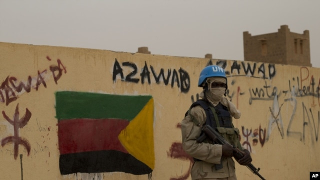 FILE - A United Nations peacekeeper stands guard at the entrance to a polling station covered in separatist flags and graffiti supporting the creation of the independent state of Azawad, in Kidal, Mali, July 28, 2013.