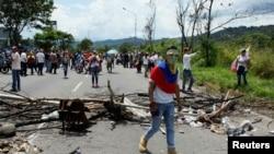 A demonstrator walks past a barricade during a rally demanding a referendum to remove Venezuela's President Nicolas Maduro in San Cristobal, Venezuela, Oct. 26, 2016.