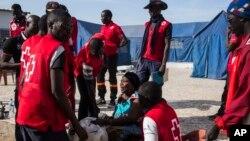 Les éléments de la Croix rouge assistent Fatou Jeng, au centre, après sa traversée à la frontière gambienne avec son enfant, dans le village de Karanga, Sénégal, 19 janvier 2017.
