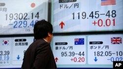 Một người đàn ông đang xem bảng ghi tỷ giá giao dịch ngoại tệ ở Tokyo, Nhật Bản.