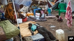 FILE - A sick displaced man lies asleep on a bed while a mother bathes her son and keeps an eye on her other child in the United Nations camp in Juba, South Sudan, Feb. 12, 2014.