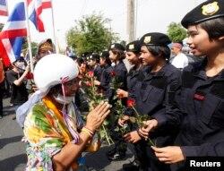 一位反政府示威者12月3日在曼谷的警察总部前向警察献上玫瑰花