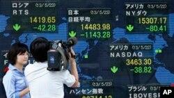Seorang juru kamera tengah menyoroti indikator elektronik yang terpampang di luar gedung sebuah perusahaan sekuritas di Tokyo (23/5). Indeks Nikkei Jepang turun tajam sebanyak 7,3 persen dan berakhir dengan 1.143 poin lebih rendah dibandingkan saat pembukaan lantai bursa di pagi harinya.