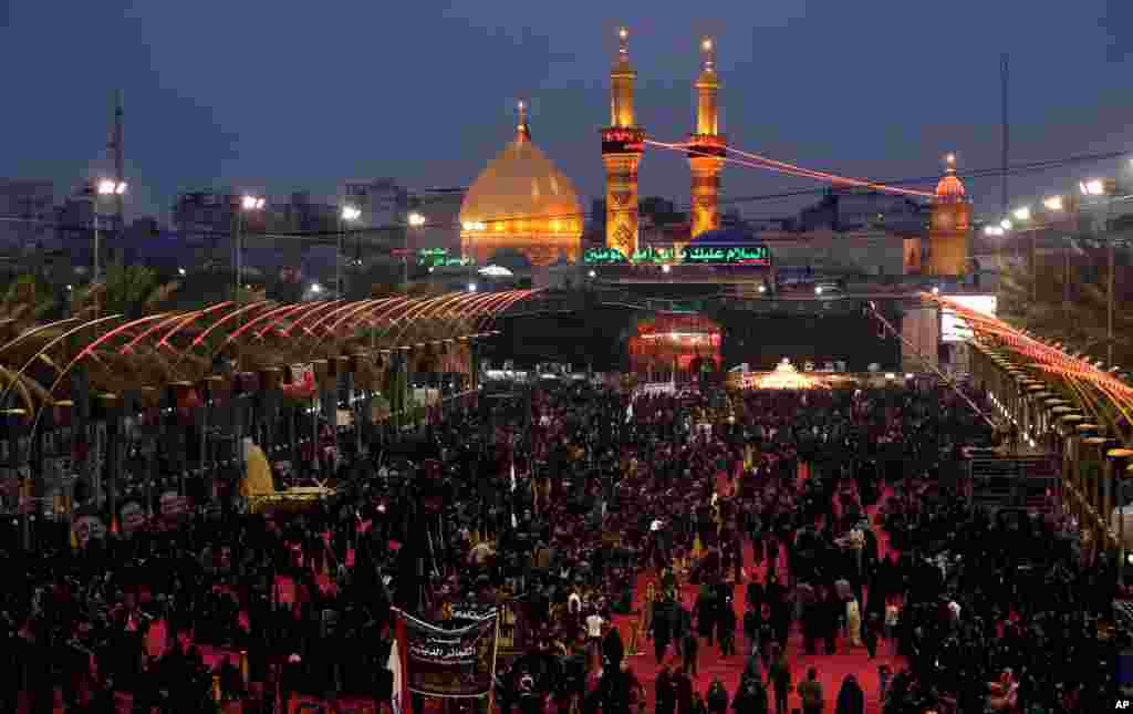 Shi'ite worshippers gather between the holy shrines of Imam Hussein and Imam Abbas, seen in the background, during Muharram in Karbala, Iraq, Nov. 12, 2013.