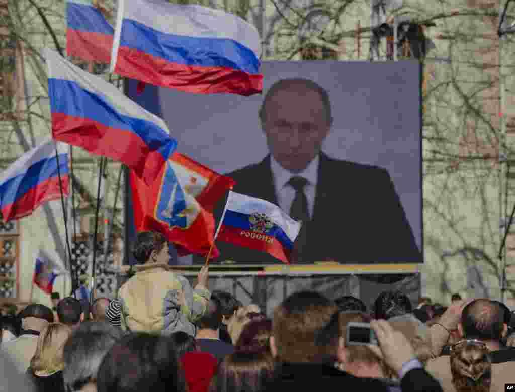 A pro-Russian crowd watches a live broadcast of Russian President Vladimir Putin's speech on Crimea, in Sevastopol, Crimea, Ukraine, March 18, 2014.