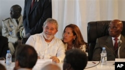 Former Brazilian President Luiz Inacio Lula da Silva, center left, speaks with a translator as he participates in a World Social Forum event with Senegalese President Abdoulaye Wade, right, at Place du Souvenir in Dakar, Senegal, Feb 7, 2011