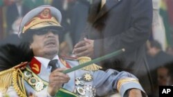 In this Sept. 1, 2009 file photo, Libyan leader Moammar Gadhafi gestures with a green cane as he takes his seat behind bulletproof glass for a military parade in Green Square, Tripoli, Libya.