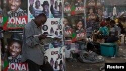 Un homme lis un journal devant une affiche de campagne électorale à Lagos, Nigéria, lundi 30 mars 2015.