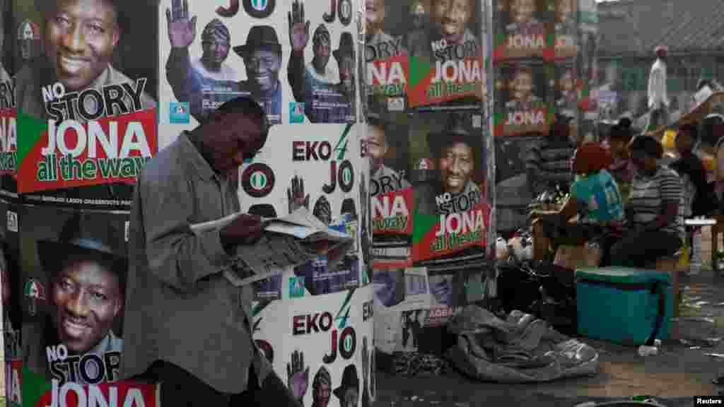 Homem lendo um Jornal na frente de pôsteres da campanha eleitoral em Lagos.