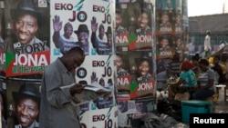在尼日利亚的拉各斯,有人在选举海报前看报(2015年3月30日)