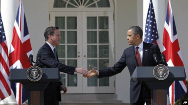 British Prime Minister David Cameron and President Barack Obama reach to shake hands during their joint news conference in the Rose Garden of the White House in Washington, March 14, 2012.