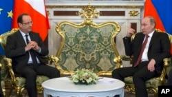 Presiden Perancis Francois Hollande (kiri) berbicang dengan President Rusia Vladimir Putin saat melakukan lawatan di Moskow (28/2).
