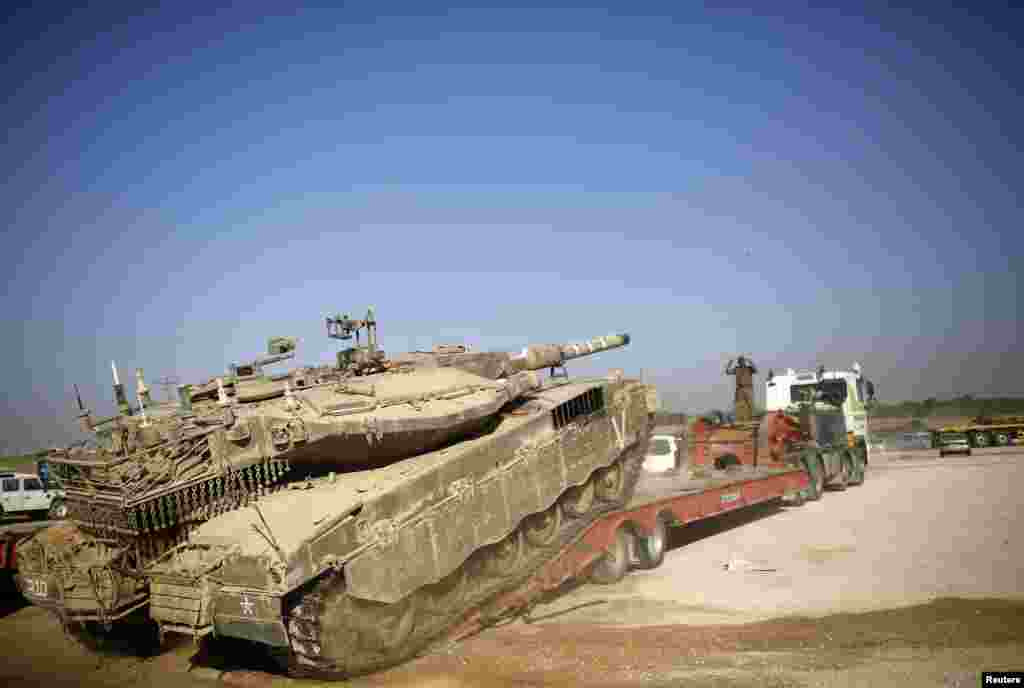 An Israeli soldier directs a tank onto a truck for transport near the border with Gaza, Aug. 6, 2014.