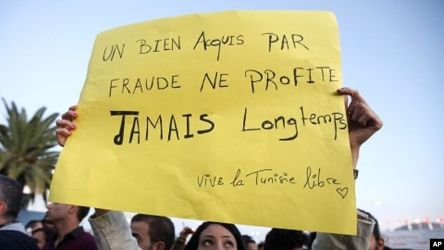 "A Tunisian demonstrator holds a sign that says ""things acquired fraudulently never last long"" during a protest against the Islamist Ennahda movement in Tunis, October 26, 2011."