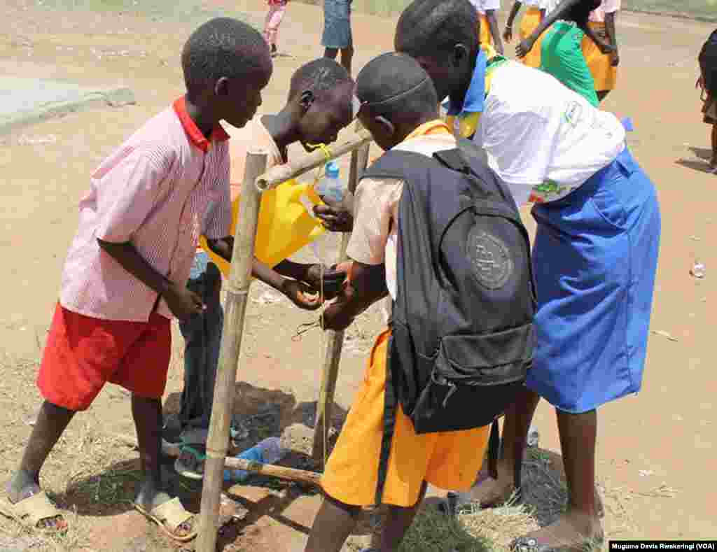 South Sudanese children wash their hands using water from a jerry can, in Juba October 2013.