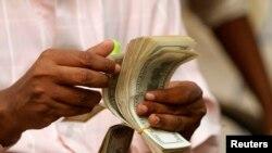 Seorang pria Somalia menghitung uangnya di kantor pengiriman uang Dahabshiil di desa Soobe, Mogadishu selatan, Somalia. (Foto: dok).