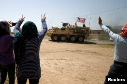 People gesture at a U.S military vehicle travelling in Amuda province, northern Syria, April 29, 2017.