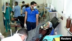A woman affected by what activists say was a gas attack on the town of Telminnes breathes through an oxygen mask at Bab al-Hawa hospital, in Syria, April 21, 2014.