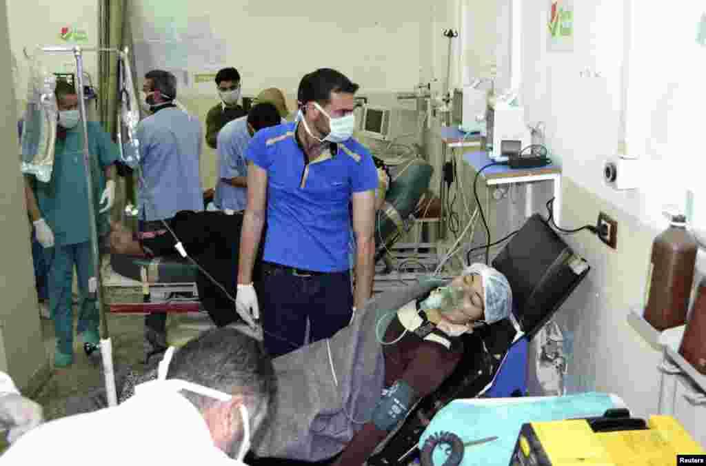 زنی که هدف حمله بمب های گازی قرار گرفته، در بیمارستان باب الحوا در مرز ترکیه با کمک ماسک اکسیژن نفس می کشد - ۲۱ آوریل ۲۰۱۴