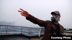 Džoš Foks pokazuje smog na krovu jedne zgrade u Pekingu